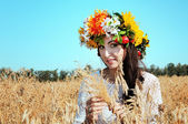 Beautiful girl in wreath in the field — Foto Stock