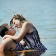 Young couple kissing in the water — Stock Photo