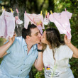 Pregnant woman and her husband with child clothes outdoor — Stock Photo