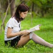 Student reading the book. Beautiful young woman with book sitting on the grass and leaning to the tree. Outdoor. — Stock Photo