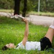 Photo: Student reading book. Beautiful young womwith book sitting on grass and leaning to tree. Outdoor.