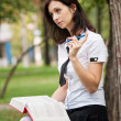Girl reading a book on the street. Schoolgirl do their homework at the park. A girl writes in a notebook — Stock Photo