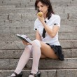 Stockfoto: Young girl with notebook in hand eating apple.