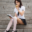 图库照片: Young girl with notebook in hand eating apple.