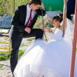 Happy bride and groom on swing at wedding day — Stock fotografie