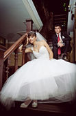 Bride and groom sitting on the stairs — Stock Photo