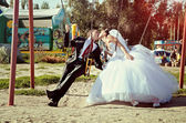 Happy bride and groom on swing at wedding day — Stock Photo