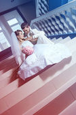 Newly merried couple sitting on stairs — Stock Photo