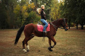 Young blond woman in blue jeans on a horse — Stock Photo