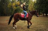 Młoda blond kobieta w dżinsach na koniu — Zdjęcie stockowe