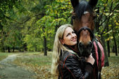 Portrait of blonde woman with horse — Stock Photo