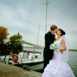Bride and groom posing on the background of sea and yacht — Stock Photo