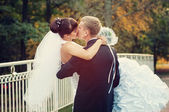 Happy just married couple kissing on the small bridge — Stock Photo