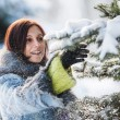 图库照片: Pretty girl shakes off snow from fir-tree