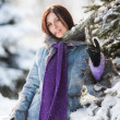 图库照片: Pretty girl standing near fir-tree in winter park