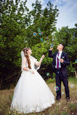 Young newly married couple blowing bubbles — 图库照片