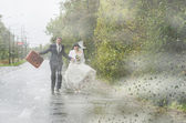 Young newlywed couple with suitcase on a rainy road — Stockfoto
