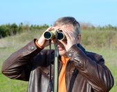 Um homem olha através de binóculos — Fotografia Stock