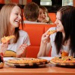 Beautiful young women eating pizza — Stockfoto