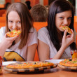 Beautiful young women eating pizza — Stock Photo #13623475