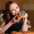Beautiful college student in pizzeria — Stock Photo