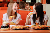Beautiful young women eating pizza — Stock Photo