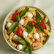 Pasta salad with cherry tomatoes and basil leaves — Stock Photo