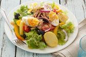 Nicoise salad over wood background — Stock Photo