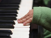 Child hand in green sleeve playing the piano — Stock fotografie