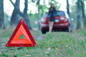 Emergency road sign with a young girl and a car in the backgroun — Stock Photo