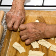 Hands of grandmother at cooking - Stock Photo