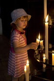 Little girl with the candles at church — Stock Photo