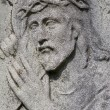 Stock Photo: Jesus with cross - stone relief