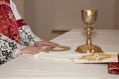 Hands of priest by the mass and the cap — Stock Photo