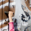 Curiosity of little girl - hand and door of street — Stock Photo
