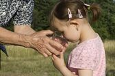 Thirst of grandchild and hands of grandmother — Stock Photo