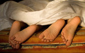 Feet of sisters in the bed — Stock Photo