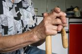 Hand of old woman and staff — Stock Photo