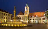 BRATISLAVA, SLOVAKIA - JANUARY 23, 2014: Main square in evening dusk with the town hall and Jesuits church. — Stock Photo