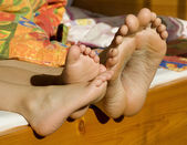 Feet of mother and child in bed — Stock Photo