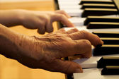 Hands of old piano player and grandchild — Stock Photo