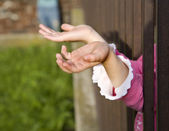 Hands of little girl and grate — Stock Photo