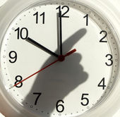 Shadow of hand on the clock — Stock Photo