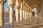 Venice - Exterior corridor of Doge palace and church Santa Maria della Salute in background. — Stock Photo