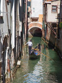VENICE, ITALY - MARCH 12, 2014: Gondolier on the little canal in center of the town. — Stock Photo