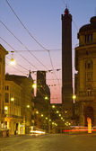 BOLOGNA, ITALY - MARCH 15, 2014: Torre Asinelli and Torre Garisenda towers at dusk from Via Rizolli. — Stock Photo