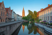 Bruges - Look to canal from Sint Jan Nepomucenus bridge with the tower of Our Lady church in morning light. — Stock Photo