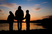 Mother and daughters over Danube under Devin ruins in Slovakia  - silhouette — Stock Photo