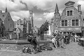 Брюгге - взгляд из rozenhoedkaai в Брюгге с уличный музыкант и Перес де malvenda дом и Бельфоре Ван Брюгге на заднем плане. — Стоковое фото