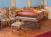 SAINT ANTON, SLOVAKIA - FEBRUARY 26, 2014: Piano in music saloon in palace Saint Anton with the handmade needlework on the chairs from 19. cent. — Stock Photo
